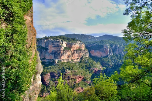 Fotografie, Obraz Orange massive rock on green mountainside covered with trees, climbing sector