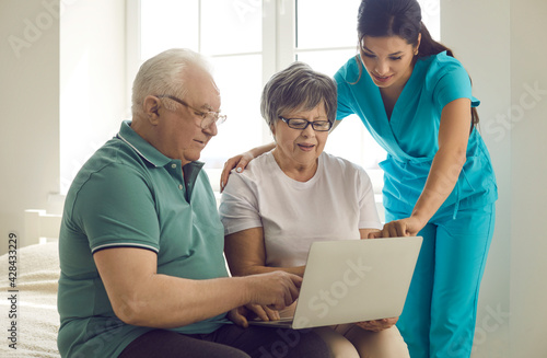 Caregiver, home care nurse or retirement home worker teaching happy senior patients to use modern computer. Old married couple looking at laptop screen and learning to browse medical Internet platform
