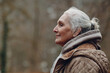 Leinwandbild Motiv Portrait profile of smiling gray haired elderly woman outdoor