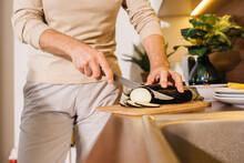 Senior Man Chopping Eggplant On Wooden Board While Preparing Dinner