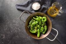 Peppers De Padron Or Fresh Green Pimientos In An Iron Pan With Olive Oil And Coarse Sea Salt, Ingredients For Spanish Tapa Or Appetizer, Dark Slate Background, Copy Space, High Angle View From Above