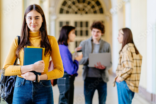 Foto Portrait of smiling female student group inside college building with students on background