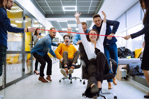 Fototapeta Friendly work team  ride chairs in office room cheerfully excited diverse employees laugh while enjoying fun work break activities, creative friendly workers play a game together