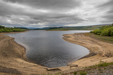 Low Water Level On A UK Reservoir. Water Shortage In Drought Conditions