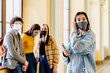 Portrait of young white girl student wearing protective mask wearing jeans jacket and striped shirt posing in university hall with other students on blurred background and pile or books.