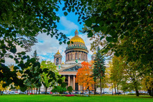 Isaac's Cathedral In Saint Petersburg. Russia In Autumn Day. Museum In The Center Of St. Petersburg. St. Isaac's Square On Background Blue Sky. Isaac's Cathedral In Crowns Of Trees. Cities Of Russia
