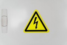 A Shield With A Yellow Triangle And A Lightning Bolt Signifies High Voltage.