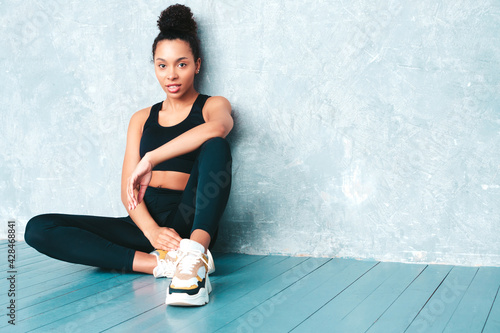 Fotografija Fitness smiling black woman in sports clothing with afro curls hairstyle