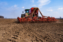 Tractor With Seeder In The Field In Early Spring