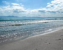 Dia Soleado Con Alguna Nuble Con El Mar Cristalino Y Pequeñas Olas Con Montañas En El Horizonte