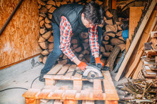 Handsome Man Cuts The Wood With A Circular Saw, Cutting Wood For The Fireplace