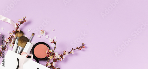 Fotografie, Obraz Set of decorative cosmetic in white paper bag with ribbons and blooming apricot twigs on light lilac background long banner format