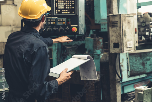 Obraz Skillful factory worker working with clipboard to do job procedure checklist . Factory production line occupation quality control concept . - fototapety do salonu