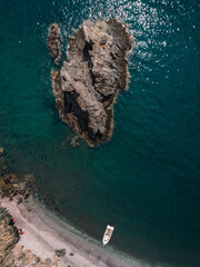 Top view shot of tropical waters, a hill island, and a white boat close to the shore