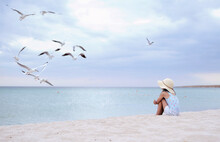 Little Cute Girl In Hat Feeds Seagulls On The Beach.