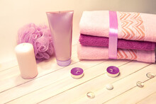 Spa Still Life - Candles, Shower Accessories And Towels On A White Wooden Background. Beige, Pink, Lilac, Purple And White Tones.