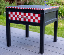 Black Painted Bedside Table With Drawer That Has Been Upcycled And Painted In Annie Sloan Chalk Paint. Drawer Is Painted In Red And White Chequered Design.