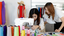 Two Asian Female Long Hair Stylish Designers Help Each Other Sew Clothes Dress Stitch With White Sewing Machine On Table Full Of Colorful Thread Rolls In Front Red Mannequin In Working Design Studio