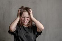 Unhappy Screaming Teenage Girl On A Dark Background
