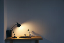 Modern Lamp And Cup Of Coffee On Table Near Light Wall In Room