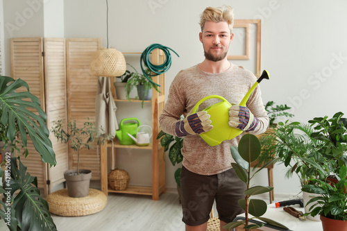 Young man taking care of plants at home Fototapet
