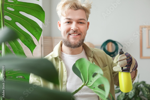 Fotografija Young man taking care of plants at home
