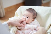 パパの指を舐めるアジア人の赤ちゃん