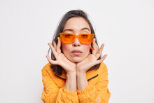 Isolated Shot Of Serious Asian Woman Keeps Hands On Cheeks Wears Tredny Orange Sunglasses And Jacket Wears Clothes Of Latest Fashion Gazes Directly At Camera Isolated Over White Studio Background