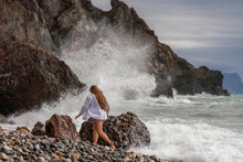 A Beautiful Girl In A White Shirt And Black Swimsuit Stands On The Edge Of A Cliff, Big Waves With White Foam. A Cloudy Stormy Day At Sea, With Clouds And Big Waves Hitting The Rocks.