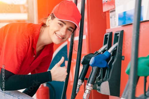 Photo Gas station women worker staff Thumbs up at fuel nozzle dispensers happy service