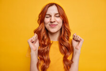 Happy Attractive Red Haired Girl Keeps Eyes Closed Clenches Fists Awaits Positive Results Anticipates Something Awesome Happen Dressed In Yellow Clothes Poses Indoor Got Approval Rejoices Success