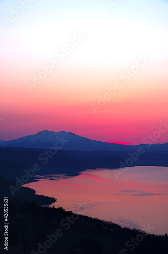 Canvas-taulu 峠から見る夜明けの空と読まの稜線のシルエット。