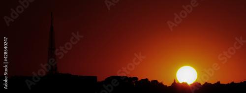 Sunset with city profile and large telecommunications antenna Fototapet