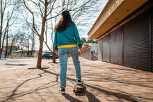 Young Beautiful Caucasian Woman Rides A Skateboard.The View From The Back. In The Background, A Street With Trees. Concept Of Sports Lifestyle And Street Culture