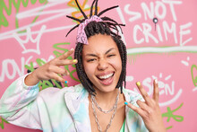 Cool Hipster Girl Makes Rap Gesture Feels Crazy And Happy Smiles Broadly Has Cheeky Expression Dressed In Stylish Clothes Poses Near Graffiti Wall. Millennial Generation Art Youth Lifestyle Concept