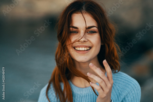 Fototapeta cheerful red-haired woman outdoors recreation travel close-up