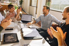 Creative Team Clapping For Young Executive In Meeting