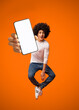 canvas print picture Funny young black teen guy jumping on air, showing cellphone with white empty screen on orange studio background, mockup