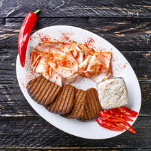 Pieces Of Bacon With Black Bread Croutons And Red Chili On A White Plate On A Black Factorial Wood Background