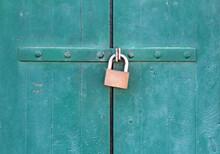 Old Green Wooden Door Locked With A Padlock