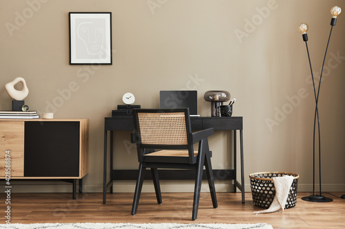 Modern interior design of home office space with stylish chair, desk, commode, black mock up poster frame, lapatop, book, office supply and elegant presonal accessories in home decor. Template. - fototapety na wymiar