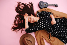 Cheerful Cheeky Young Woman Lying On The Floor, Over Pink