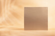 canvas print picture Gold Paper sheet or blank card with realistic leaf shadows. Creative background with empty sheet of paper with copy space.