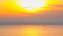 A Little Yacht Sailing On Sea At Amazing Sunset