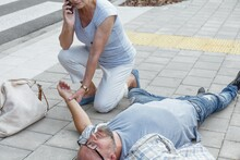Senior Passerby Kneels Beside The Person Who Fainted On The Street And Calls An Ambulance