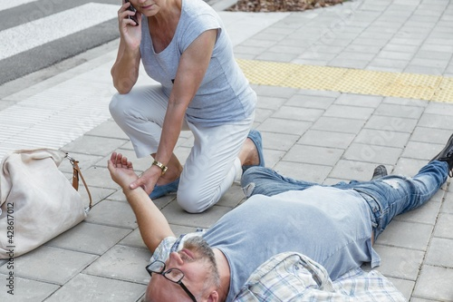 Tableau sur Toile Senior passerby kneels beside the person who fainted on the street and calls an