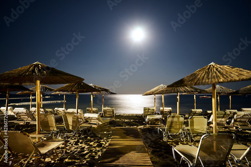 Fototapeta empty sun loungers and umbrellas on sandy beach under moonlight at night in Zaky