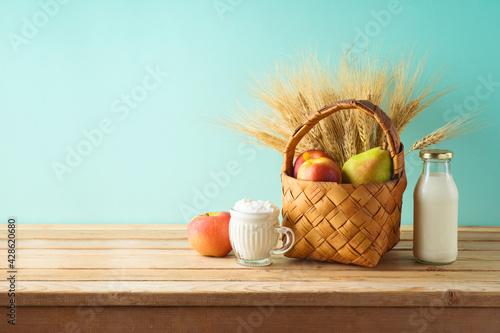 Fototapeta Jewish holiday shavuot background with fruit basket and milk bottle on wooden table obraz