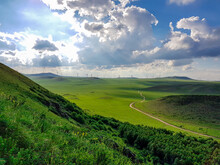 A Panoramic View On A Hilly Landscape Of Xilinhot In Inner Mongolia. Endless Grassland With A Few Wind Turbines Between. Blue Sky With Thick, White Clouds. A Small Gravel Road Through The Pasture.