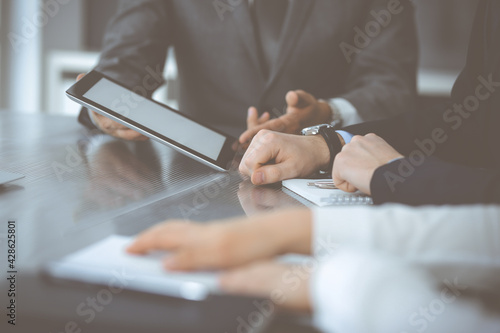 Unknown businessman using tablet computer and working together with his colleague while sits at the glass desk in modern office. Teamwork and partnership concept - fototapety na wymiar